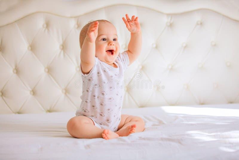 Bebé lindo en el dormitorio soleado blanco foto de archivo libre de regalías