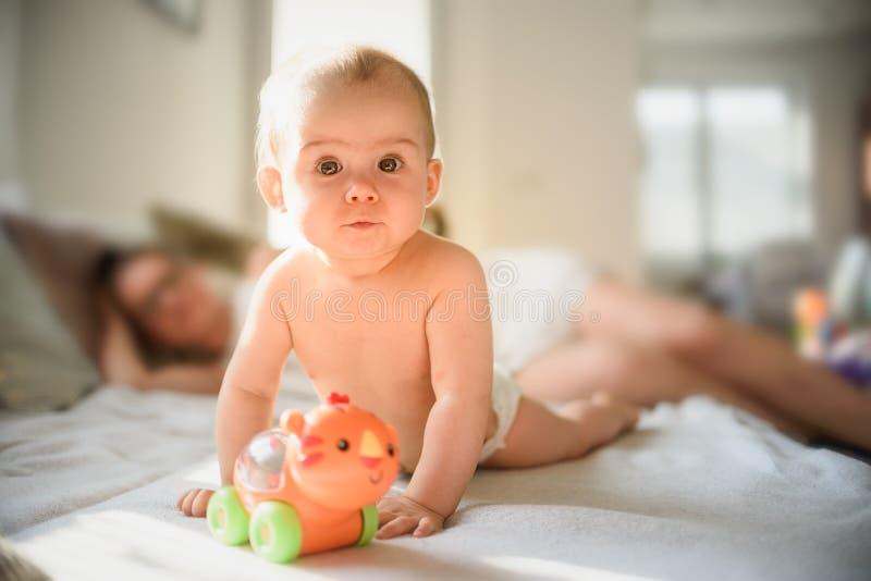 Bebé lindo en el vientre en el sofá en pañal con un juguete en el sofá imágenes de archivo libres de regalías