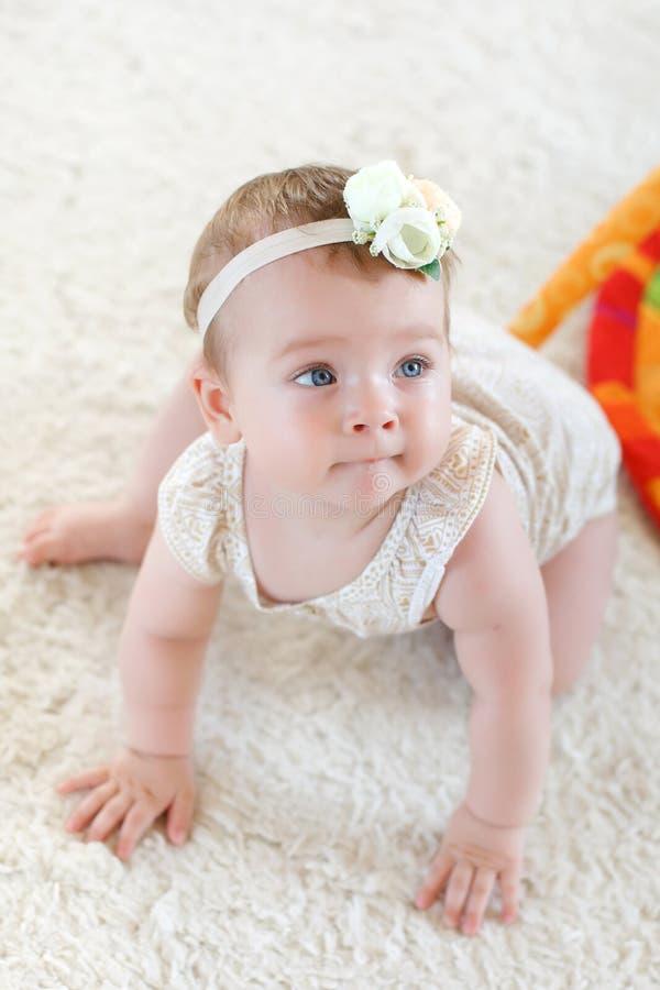 Bebé lindo en la alfombra blanca foto de archivo