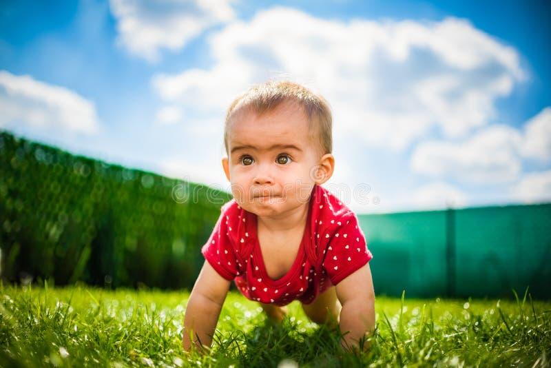 Bebé lindo en todos los fours en cuerpo rojo en hierba verde con el cielo azul y las nubes imágenes de archivo libres de regalías