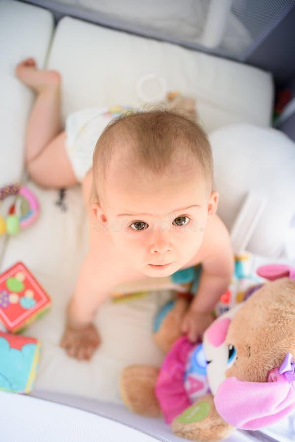 Bebé lindo en todos los fours en un pesebre del bebé fotografía de archivo