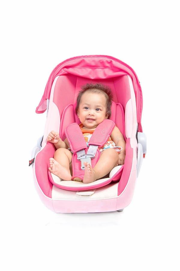 Bebé lindo en un asiento de carro, aislado foto de archivo