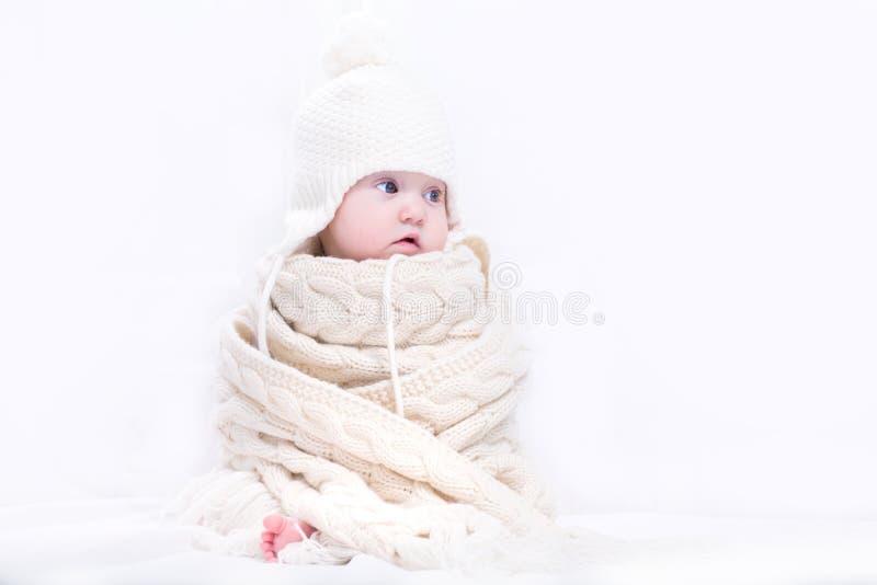 Bebé lindo en una bufanda y un sombrero hechos punto grandes fotos de archivo libres de regalías