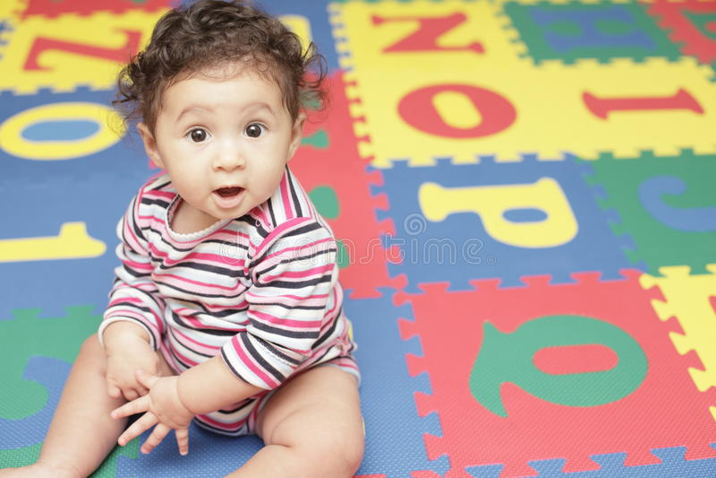 Bebé lindo en una estera del juego imagen de archivo libre de regalías