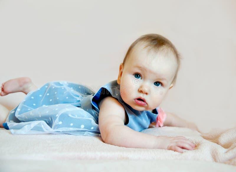 Bebé lindo en vestido azul con la flor rosada fotos de archivo libres de regalías