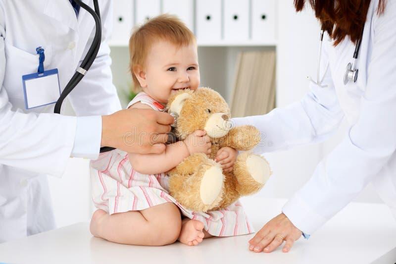 Bebé lindo feliz en el examen de la salud en la oficina del ` s del doctor Concepto de la medicina y de la atención sanitaria fotografía de archivo