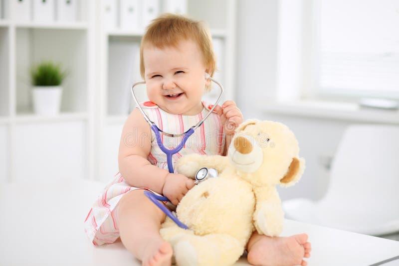 Bebé lindo feliz en el examen de la salud en la oficina del ` s del doctor Concepto de la medicina y de la atención sanitaria foto de archivo libre de regalías