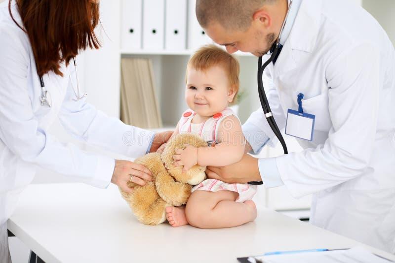 Bebé lindo feliz en el examen de la salud en la oficina del ` s del doctor Concepto de la medicina y de la atención sanitaria imagenes de archivo