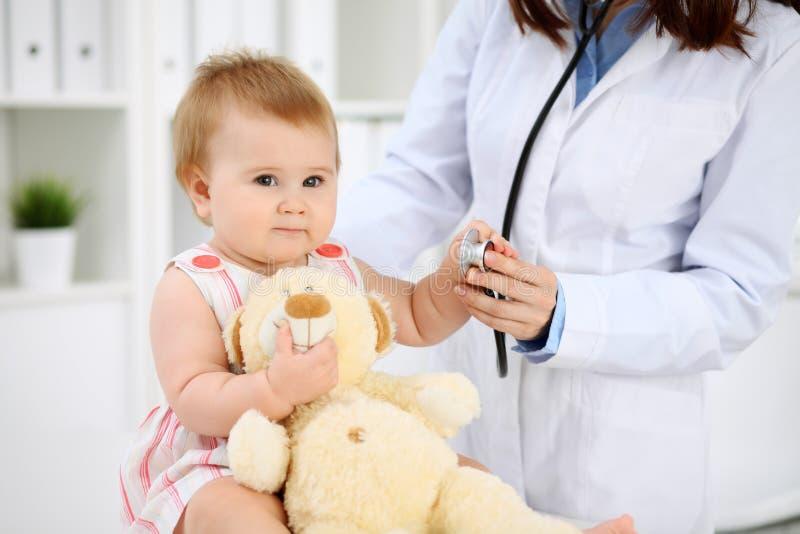 Bebé lindo feliz en el examen de la salud en la oficina del ` s del doctor Concepto de la medicina y de la atención sanitaria imágenes de archivo libres de regalías