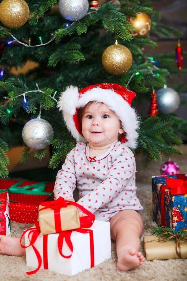 Bebé lindo feliz en el sombrero de Santa Claus que sostiene los regalos de la Navidad en el árbol de navidad en casa imágenes de archivo libres de regalías