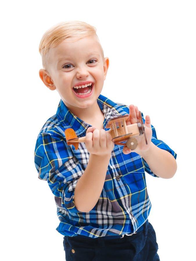 Bebé lindo feliz que juega con un aeroplano del juguete y que ríe alegre Aislado en blanco foto de archivo