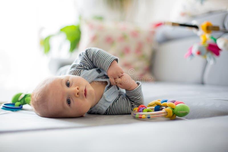 Bebé lindo, jugando con los juguetes en una sala de estar soleada fotos de archivo