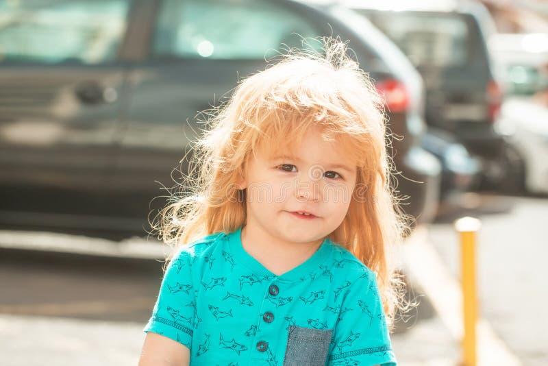 Bebé lindo que camina en la calle de la ciudad foto de archivo