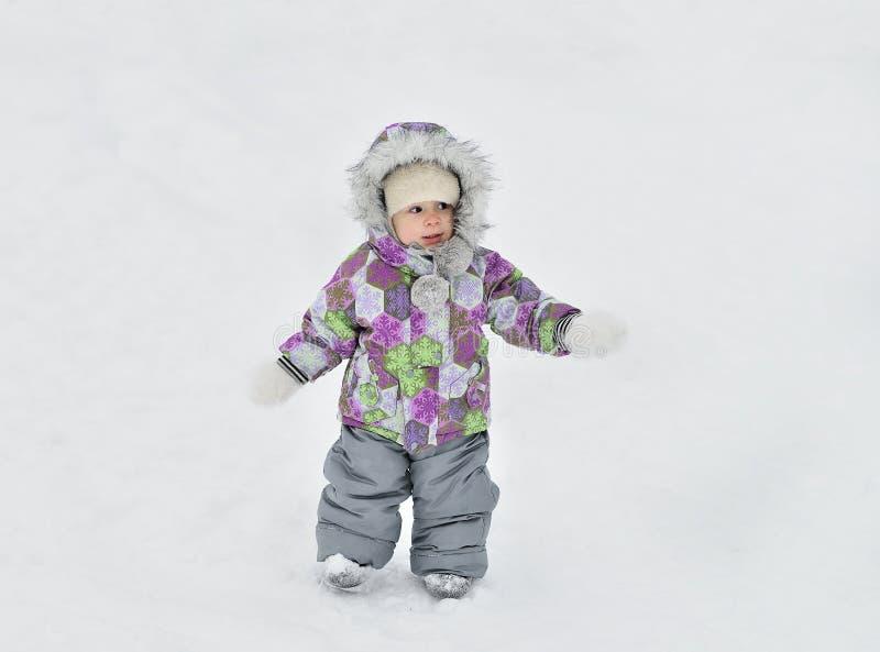 Bebé lindo que camina a través del parque del invierno cubierto con nieve foto de archivo libre de regalías
