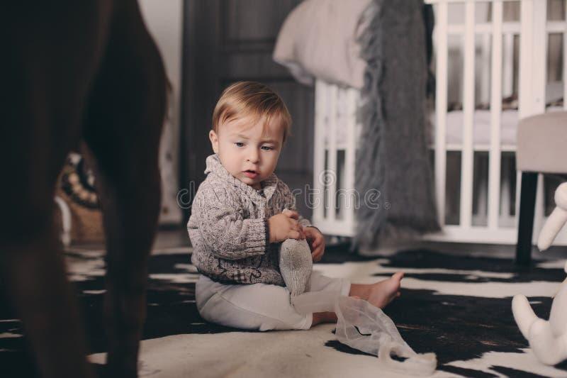 Bebé lindo que come las galletas y que juega en casa Interior sincero del captute en la vida real foto de archivo libre de regalías