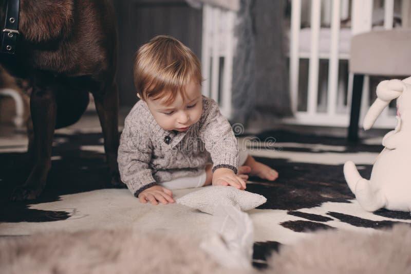 Bebé lindo que come las galletas y que juega en casa Interior sincero del captute en la vida real imagen de archivo libre de regalías