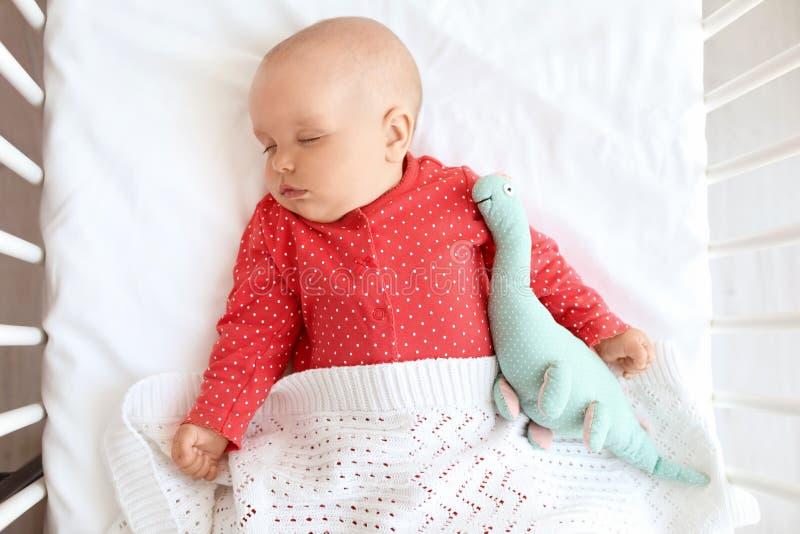 Bebé lindo que duerme en pesebre fotos de archivo