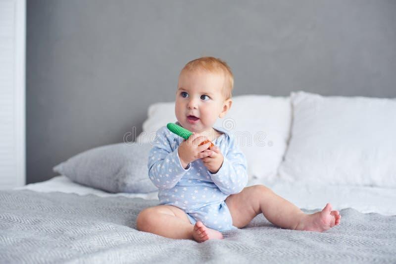 Bebé lindo que juega con el juguete hecho punto en cama en casa foto de archivo