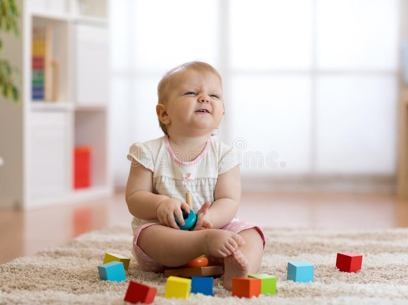 Bebé lindo que juega con los juguetes en sala de estar imagen de archivo
