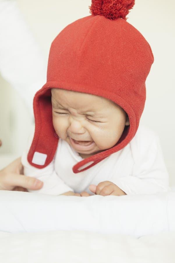 Bebé lindo que llora en el pesebre imagenes de archivo