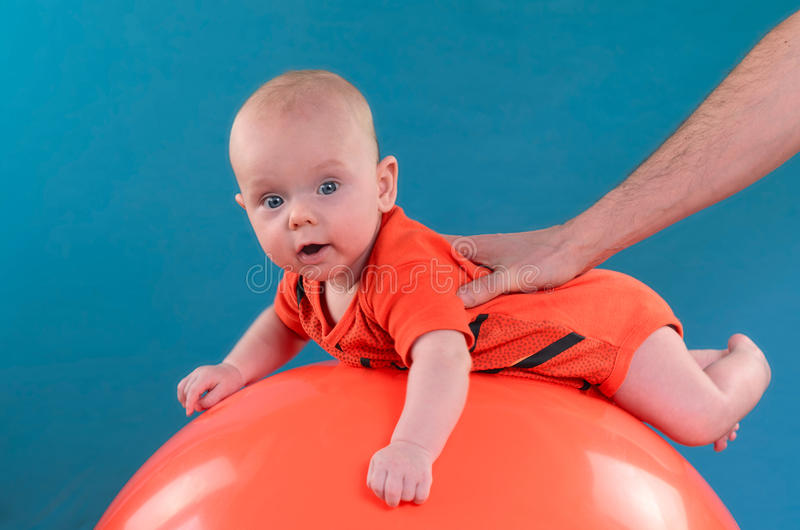 Bebé lindo que miente en el fitball anaranjado en el fondo azul Co imagen de archivo