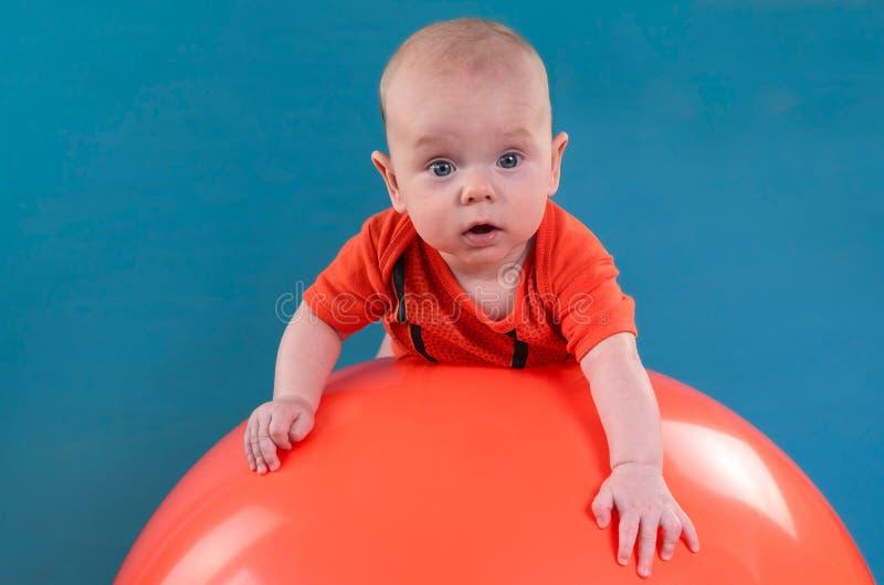 Bebé lindo que miente en el fitball anaranjado en el fondo azul Co fotos de archivo libres de regalías