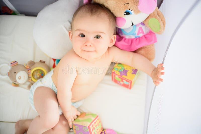 Bebé lindo que miente en el pesebre que mira para arriba y que sonríe foto de archivo libre de regalías