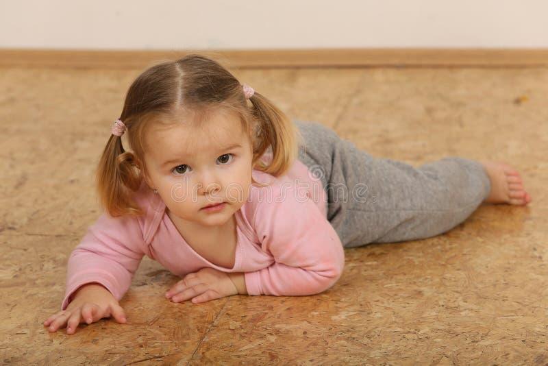 Bebé lindo que miente en piso imagen de archivo