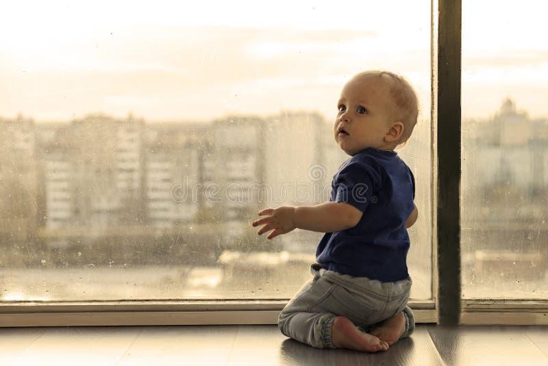 Bebé lindo que mira a través de la ventana a la ciudad grande lluviosa Niño pequeño que espera a los padres Sentada del niño del  fotos de archivo