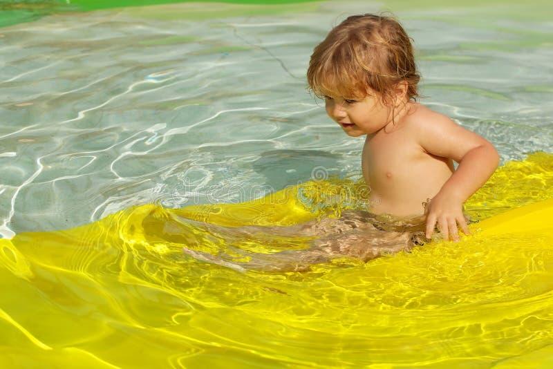 Bebé lindo que resbala del waterslide amarillo imagen de archivo