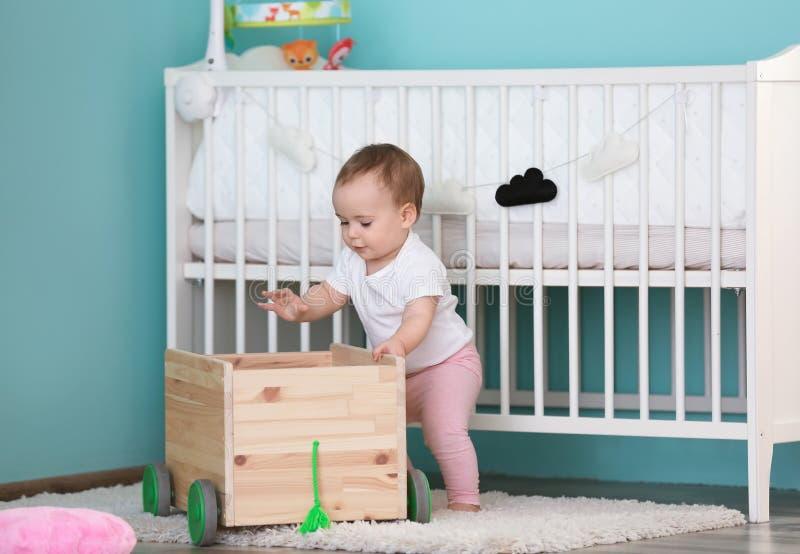 Bebé lindo que se aferra al carro de madera en sitio de niños fotografía de archivo