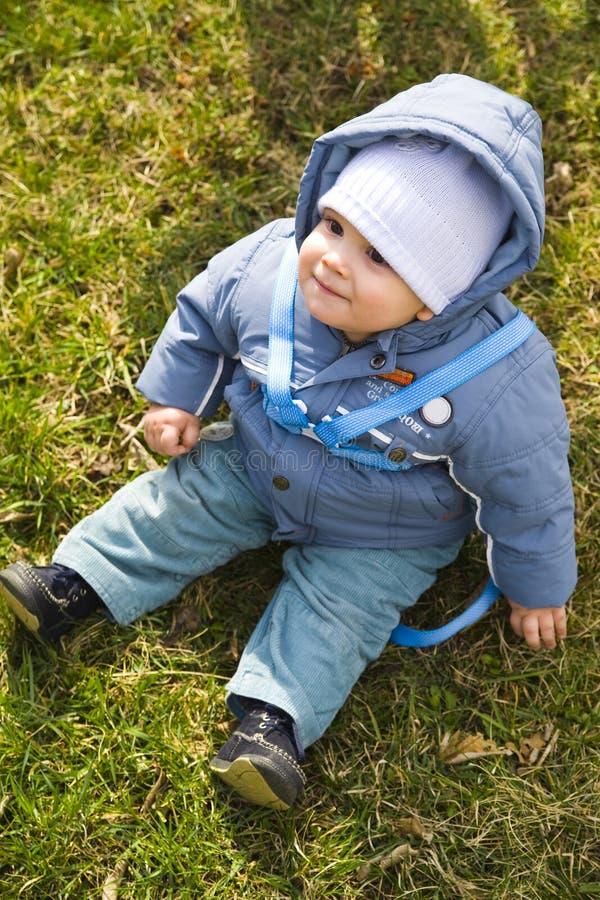 Bebé lindo que se sienta en hierba fotografía de archivo