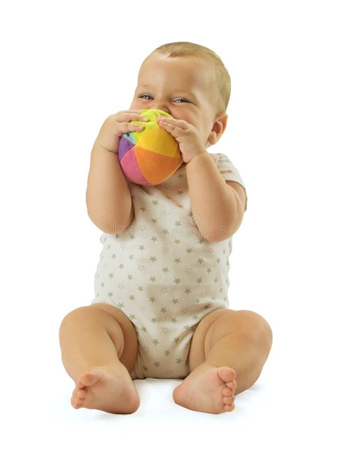Bebé lindo que sostiene la bola delante de su cara y sonrisa Aislado en el fondo blanco foto de archivo