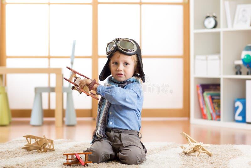 Bebé lindo que sueña con ser piloto Muchacho del niño que juega con los aeroplanos del juguete imagenes de archivo
