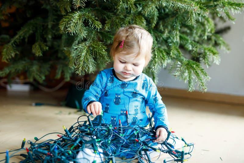 Bebé lindo que toma abajo de decoraciones del día de fiesta del árbol de navidad niño que sostiene la guirnalda ligera imágenes de archivo libres de regalías