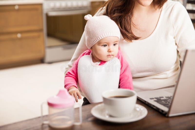 Bebé lindo que trabaja con su mamá imagenes de archivo