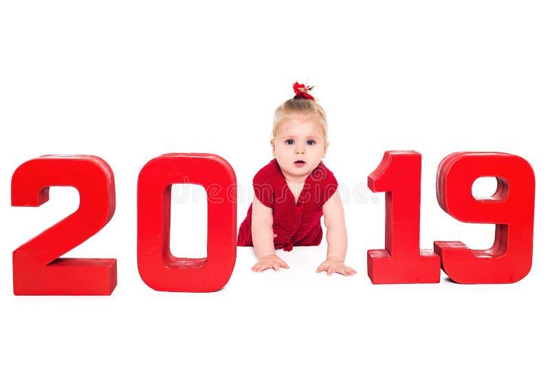 Bebé lindo sorprendido con los números rojos 2019, aislados sobre el fondo blanco imagen de archivo