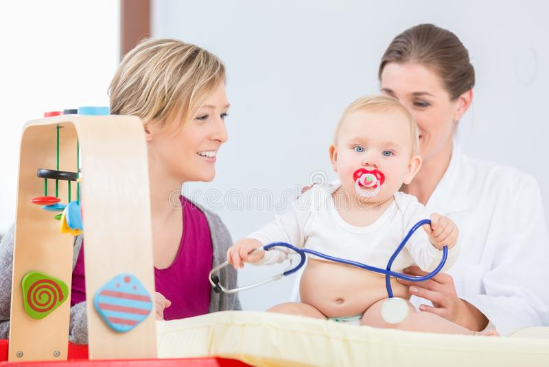 Bebé lindo y sano que juega con el estetoscopio durante el examen fotografía de archivo