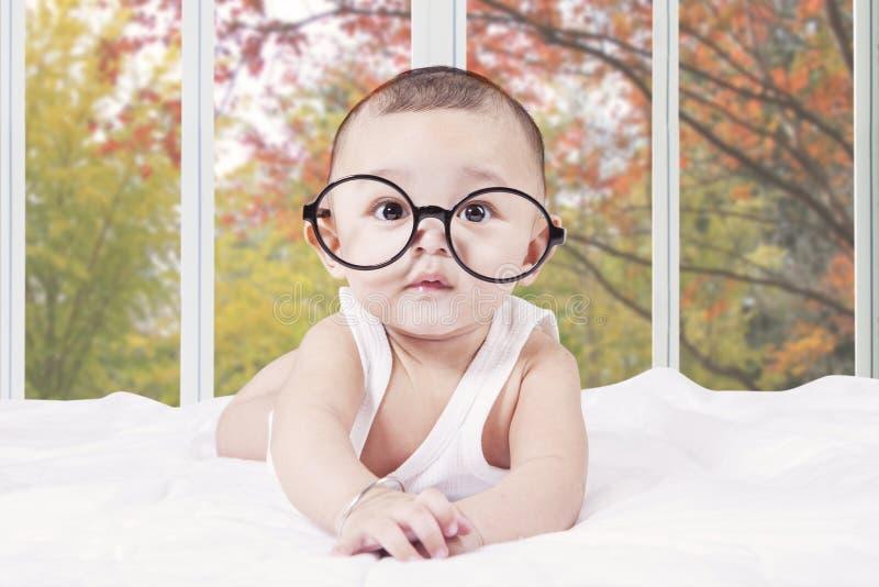 Bebé masculino con los vidrios que mienten en cama imagenes de archivo