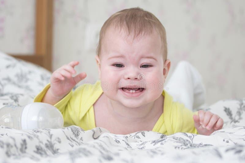 Bebé 6-7 meses de mentira gritadora en su estómago Un bebé caucásico en amarillo es gritador y que muestra 2 dientes de bebé, den fotografía de archivo libre de regalías