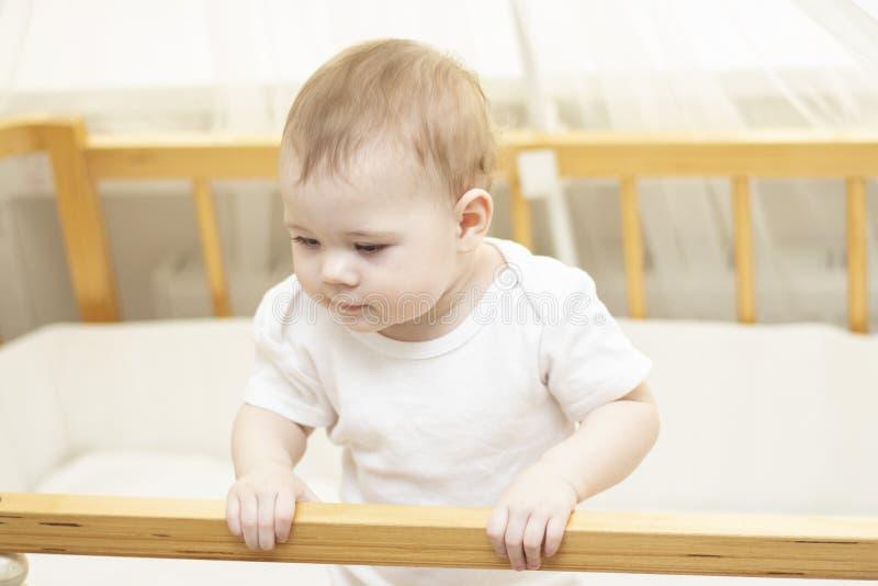 Bebé 8 meses en las miradas blancas fuera de la cuna El bebé lindo conoce el mundo, un niño curioso se aferra en el borde del pes fotografía de archivo libre de regalías