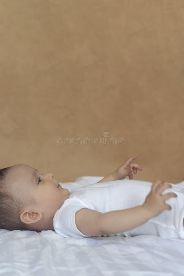 bebé 6-8-month-old que miente juguetónamente en cama Pequeño bebé encantador del mes 6-7 en el mono blanco Bebé en el lecho blanc imagen de archivo