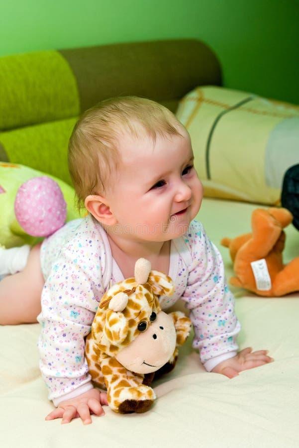 Bebé na cama com brinquedos   imagens de stock royalty free