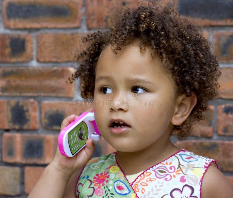 Bebé negro joven en un teléfono celular del juguete fotografía de archivo libre de regalías