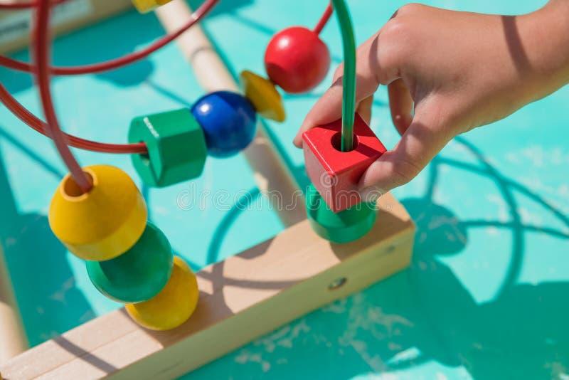 Bebé, niño que juega en cuarto de niños Niño sano feliz que se divierte con el juguete colorido en casa Laberinto colorido del ju imagenes de archivo