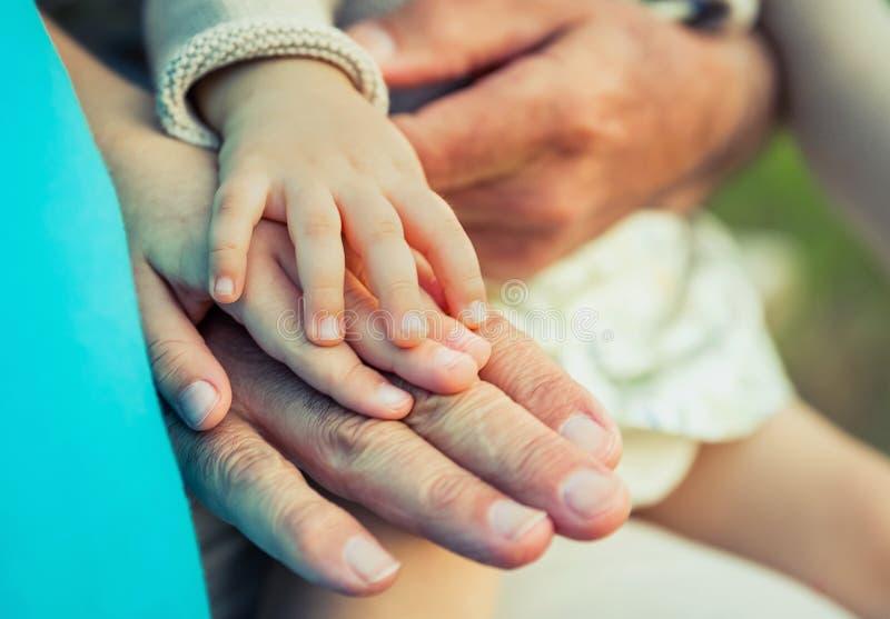 Bebé, niño y hombre mayor comparando tamaño de las manos foto de archivo