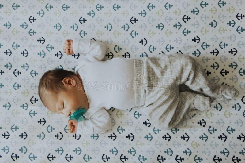 Bebé pacífico que duerme en un pesebre fotografía de archivo