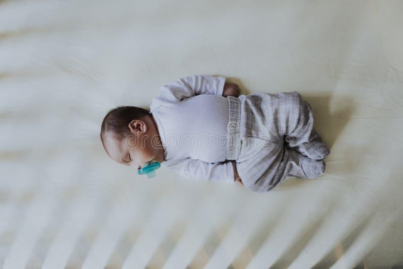 Bebé pacífico que duerme en un pesebre imagenes de archivo