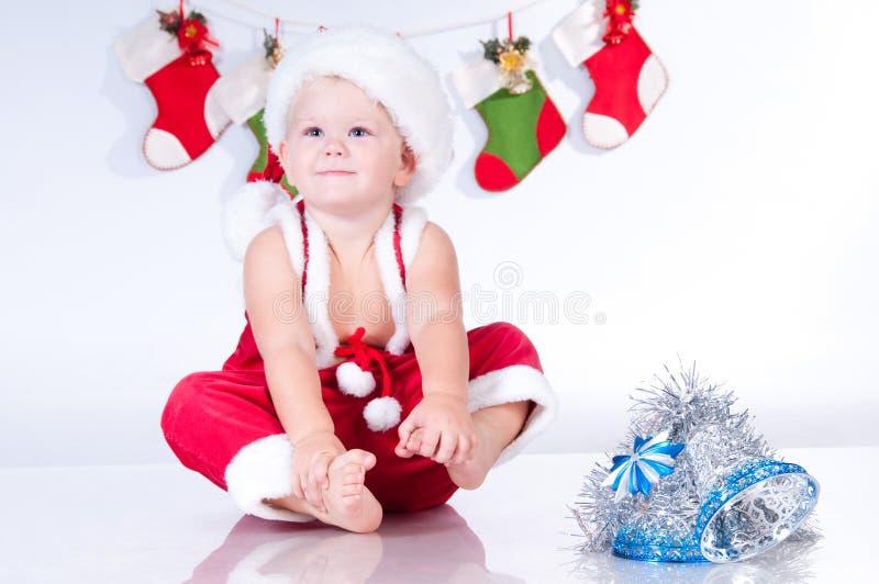 Bebé Papá Noel con las guirnaldas del bootee de la Navidad imagen de archivo