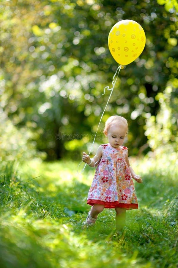 Bebé pequeno com um balão amarelo fotos de stock